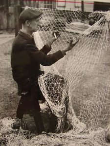 Beverly fisherman Edward Bintliff mending his shad nets in 1940